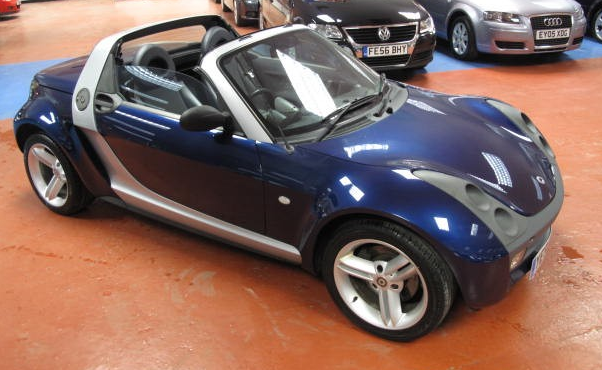 Smart convertable car in navy blue with two doors.PNG