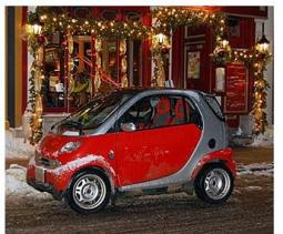 A grey and red Smart car cover with some snow.jpg
